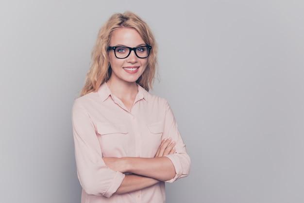 Mulher de negócios usando óculos de traje formal com as mãos postas sobre cinza