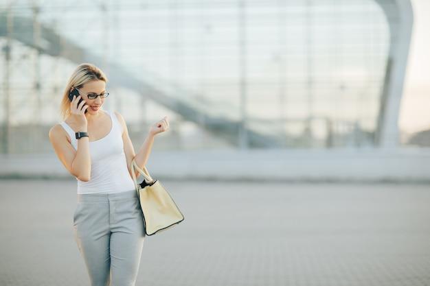 Mulher de negócios usando óculos escuros em calças cinza fala por telefone