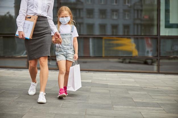 Mulher de negócios usando saia cinza e andando com a filha na rua da cidade