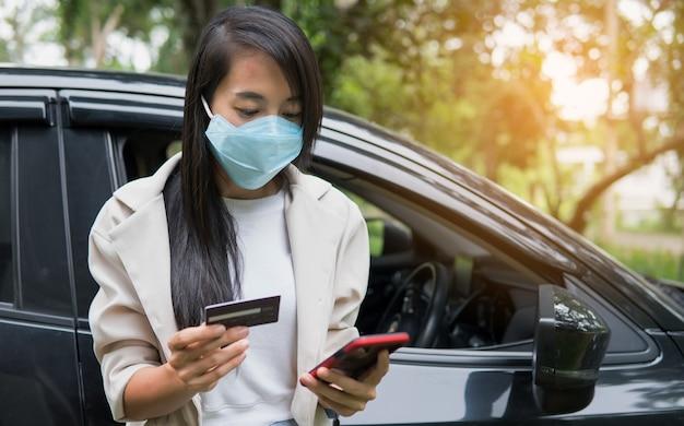 Mulher de negócios usando smartphone e cartão de crédito para fazer compras on-line no carro. novo conceito normal de negócios após o surto de coronavírus covid-19.