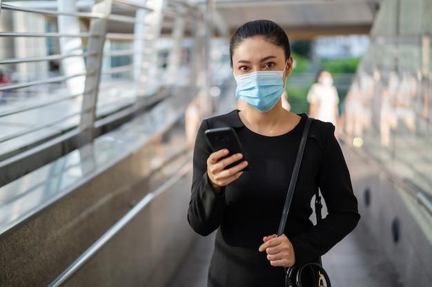 Mulher de negócios usando smartphone e máscara médica