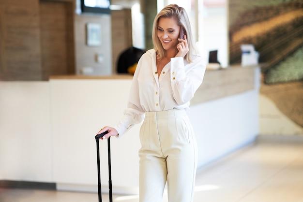 Mulher de negócios usando smartphone no saguão de um hotel moderno