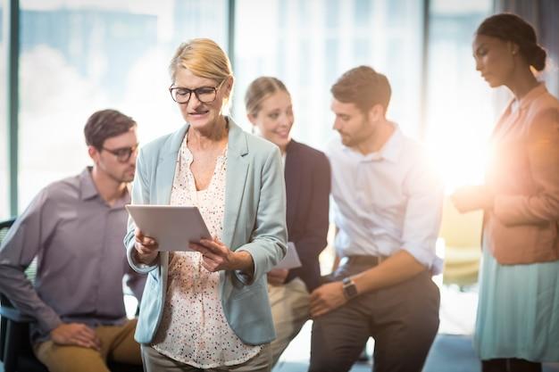 Mulher de negócios usando tablet digital enquanto colega de trabalho interagindo em segundo plano