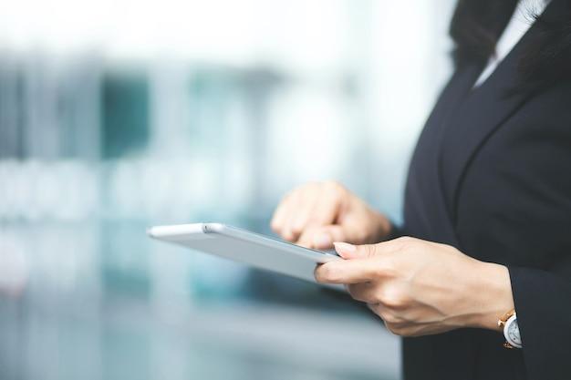Mulher de negócios usando tablet digital sobre mesa de luz