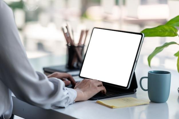 Mulher de negócios usando tablet digital, trabalhando em casa. tela branca em branco.