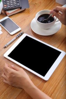 Mulher de negócios usando tablet maquete com café preto e artigos de papelaria de escritório na mesa de madeira