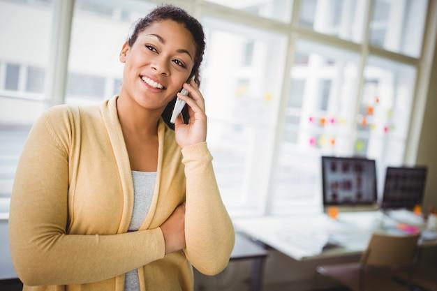 Mulher de negócios usando telefone celular no escritório criativo