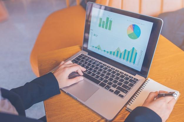 Mulher de negócios usando um computador portátil em uma mesa de madeira, e ela está tomando notas em papel com uma caneta preta no escritório, computador, mostrando a análise do gráfico de trabalho,