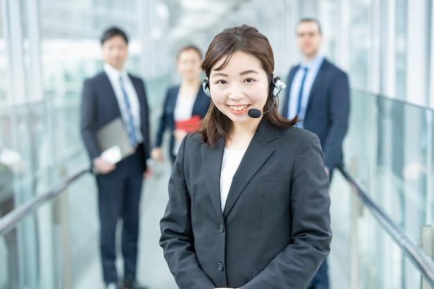 Mulher de negócios usando um fone de ouvido e sua equipe de negócios