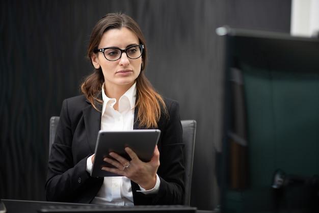 Mulher de negócios usando um tablet em seu escritório, conceito de carreira de empresária