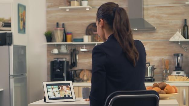 Mulher de negócios usando um tablet para videochamada durante o café da manhã. jovem freelancer na cozinha falando em uma videochamada com os colegas do escritório, usando a moderna tecnologia da internet
