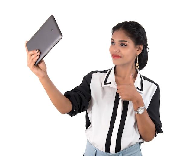 Mulher de negócios usando um telefone celular ou smartphone isolado em uma parede branca
