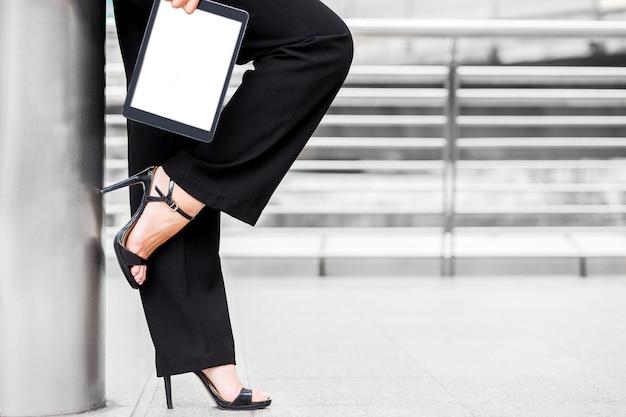 Mulher de negócios usar salto alto e segurar o tablet