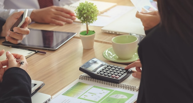 Mulher de negócios use uma calculadora para calcular. análise de figuras durante a conferência.