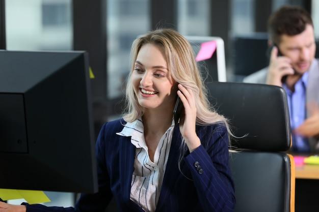 Mulher de negócios using computer at desk no escritório ao ligar para o telefone móvel