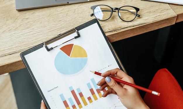 Mulher de negócios verifica gráficos e atualiza o progresso financeiro. a garota analisa o modelo de negócios no ambiente de trabalho.