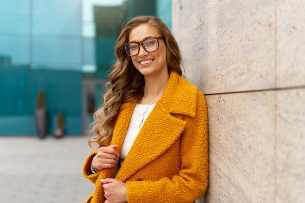 Mulher de negócios vestida de casaco amarelo em pé ao ar livre fundo de edifício corporativo óculos de mulher de negócios caucasiana na rua perto de prédio de escritórios com janelas mulher de negócios elegante