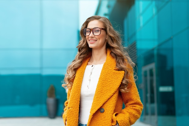 Mulher de negócios vestida de casaco amarelo em pé ao ar livre fundo de edifício corporativo óculos de pessoa de negócios do sexo feminino caucasiano na rua perto de prédio de escritórios grandes janelas mulher de negócios elegante