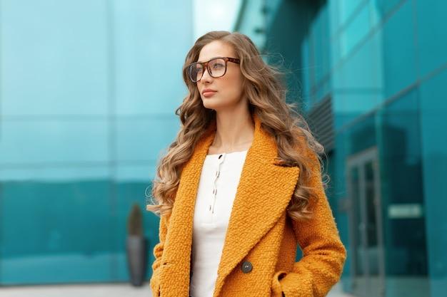 Mulher de negócios vestida de casaco amarelo em pé ao ar livre fundo de edifício corporativo óculos de pessoa de negócios do sexo feminino caucasiano na rua perto de prédio de escritórios grandes janelas.