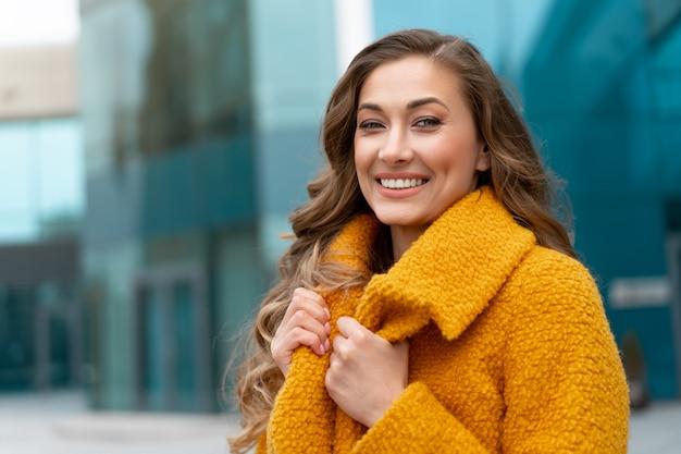 Mulher de negócios vestida de casaco amarelo em pé ao ar livre superfície do edifício corporativo mulher de negócios branca na rua perto do prédio comercial com janelas mulher de negócios elegante