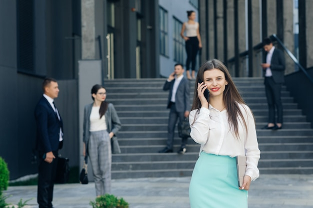 Mulher de negócios vestindo camisa branca usando telefone inteligente moderno. empregador profissional feminino digitando mensagem de texto no celular do lado de fora.