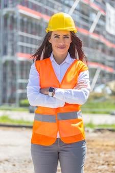 Mulher de negócios vestindo jeans, colete de segurança e capacete fica com confiança na frente da construção coberta por andaimes.