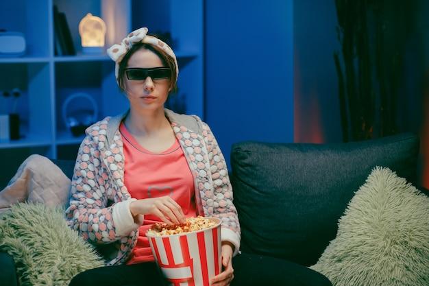 Mulher de óculos 3d comendo pipoca. divertida jovem de óculos 3d, assistindo filme, comer pipoca.