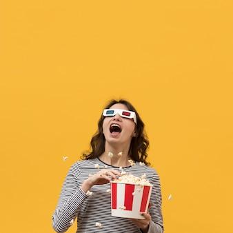 Mulher de óculos 3d segurando um balde com pipoca