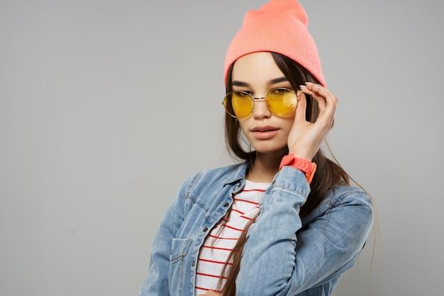 Mulher de óculos amarelos na moda de chapéu-de-rosa em estilo moderno de fundo cinza