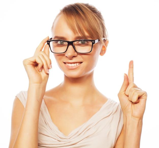 Mulher de óculos apontando para cima