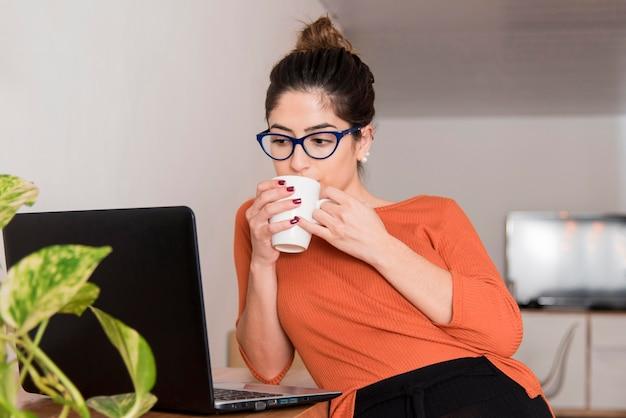 Mulher de óculos bebendo café
