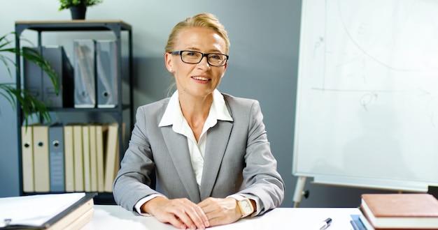 Mulher de óculos, caucasiana, sorrindo, sentada no escritório e falando via webcam, videochat e educando negócios. vídeo blog de gravação de treinadora feminina. videochat do blogger. coaching de empresária online.