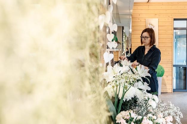 Mulher de óculos com penteado bob, morena, cuida de flores em sua loja de flores. conceito de empresa de pequeno porte, floricultura.