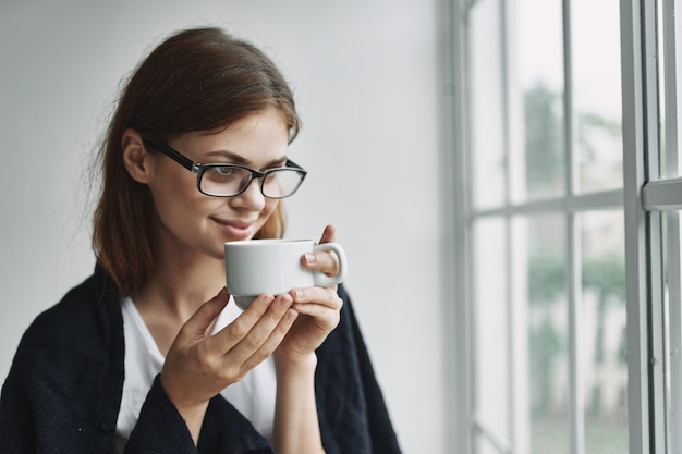 Mulher de óculos com uma xícara de chá nas mãos perto da janela da sala
