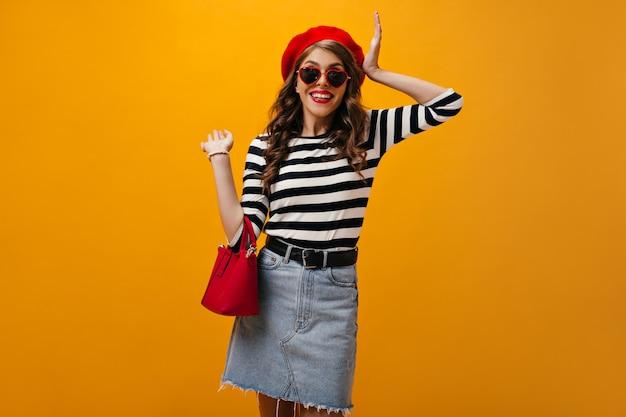 Mulher de óculos de sol em forma de coração segura bolsa vermelha. sorridente garota legal com cabelos ondulados em saia jeans e posar de suéter listrado.