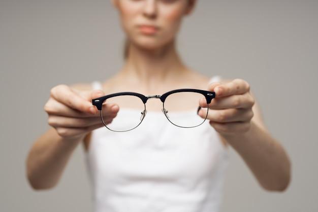 Mulher de óculos de t-shirt branca problemas de visão miopia.