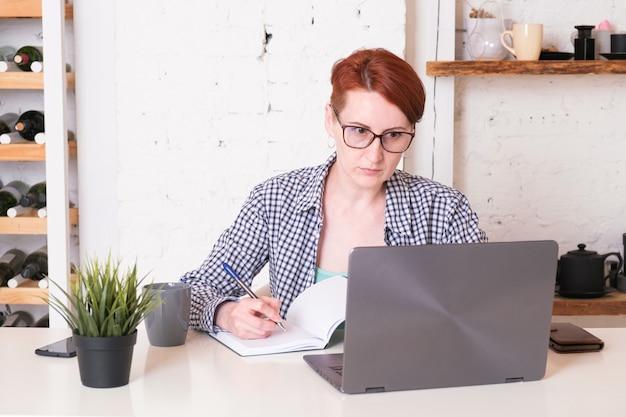 Mulher de óculos e camiseta olha atentamente para a tela do laptop e faz anotações no caderno