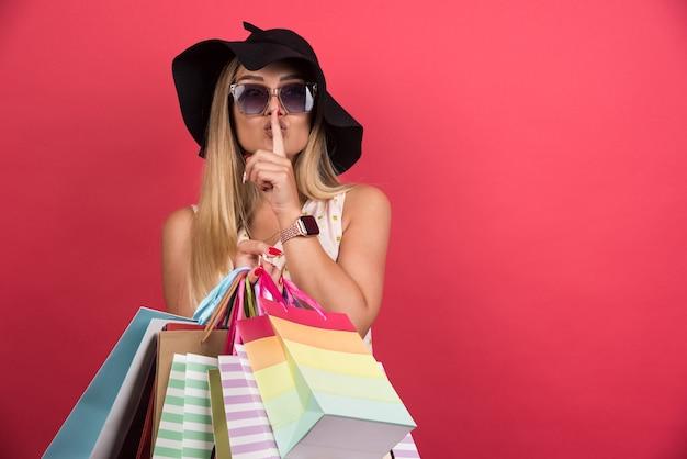 Mulher de óculos e chapéu segurando suas sacolas de compras, fazendo sinal de silêncio na parede vermelha.