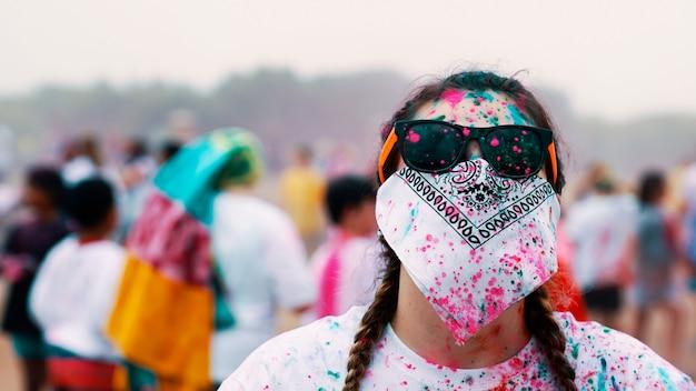 Mulher de óculos e cobrindo o rosto com uma bandana durante uma festa de pintura