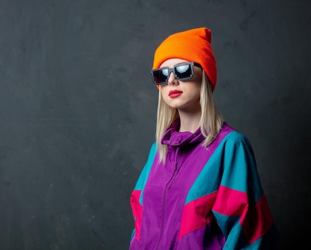 Mulher de óculos e terno esporte dos anos 80 na parede cinza