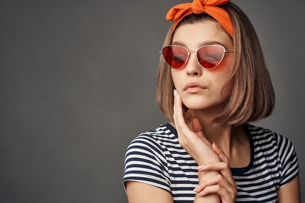 Mulher de óculos escuros com uma bandagem laranja na cabeça em uma moda de camiseta listrada. foto de alta qualidade