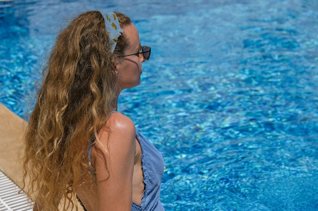 Mulher de óculos escuros e biquíni perto da piscina, tomando banho de sol nas férias.