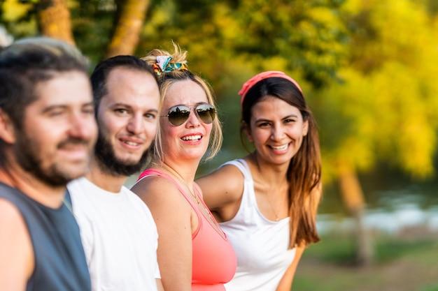 Mulher de óculos escuros em pé com um grupo de amigos em um parque