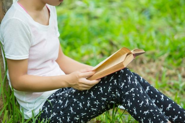 Mulher de óculos lendo livro no parque