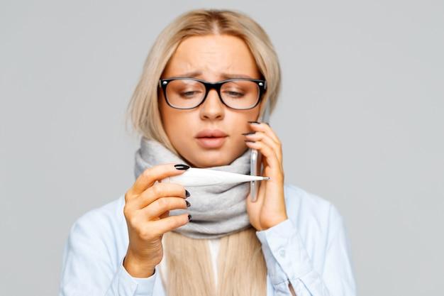 Mulher de óculos, ligando para o médico por telefone, olhando para o termômetro