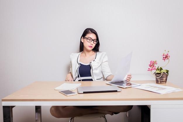 Mulher de óculos olhando documentos