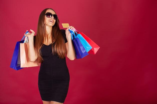 Mulher de óculos segurando sacolas de compras