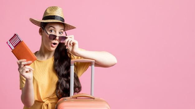 Mulher de óculos, segurando seu passaporte com espaço de cópia