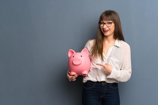 Mulher de óculos segurando um piggybank