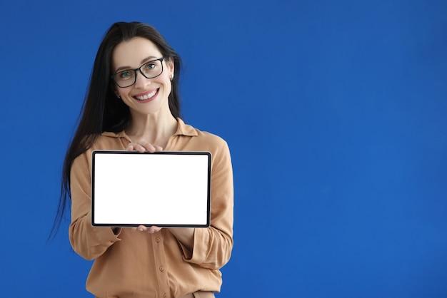 Mulher de óculos segurando um tablet digital com tela branca nas mãos